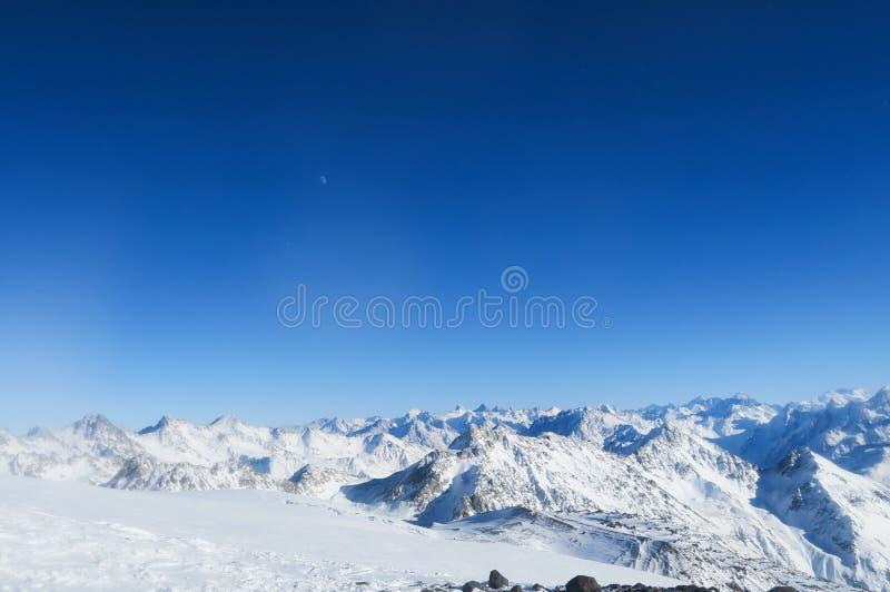 Lune au-dessus du glacier neigeux des montagnes caucasiennes dans le ciel bleu r?gion su de montagne de lac de gorge d'elbrus de  photos stock