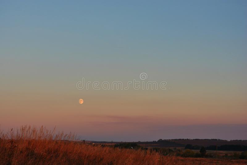 Lune de récolte se levant au-dessus des collines avec le village, soirée d'automne photographie stock libre de droits