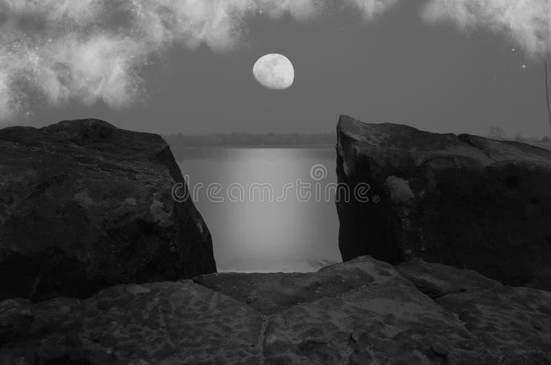 Lune et nuages de affaiblissement blancs au-dessus du lac et des roches photographie stock