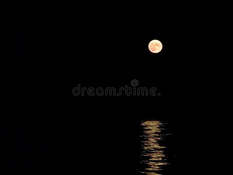 Lune se levant au-dessus de la mer images stock