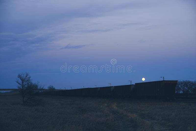 Lune se levant au-dessus du train au crépuscule, Julesburg le Colorado photo libre de droits