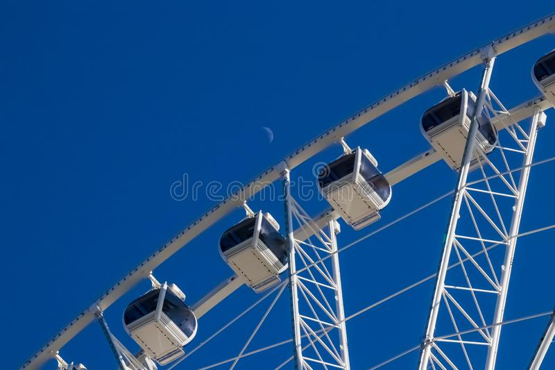 Lune se levant dans un ciel bleu clair au-dessus d'une roue de ferris photos libres de droits