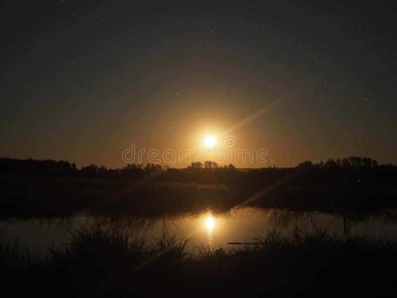 Lune se levant sous le lac photographie stock