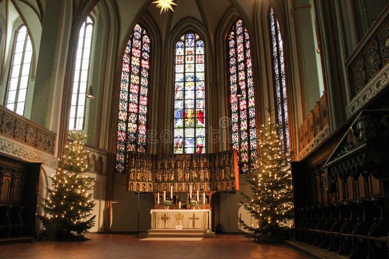 Luneburg, Germania - 10 12 2017: Altare di Natale nella chiesa cattolica e vetro macchiato dietro  fotografia stock
