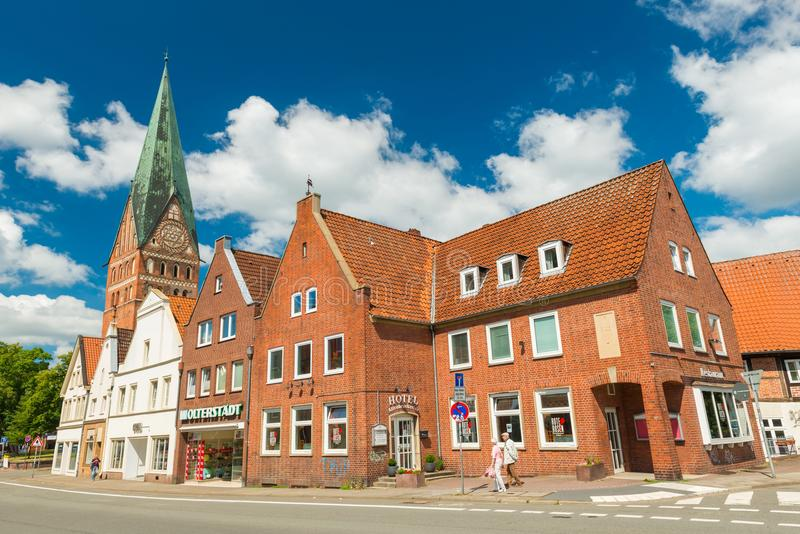 Luneburg, Germany: Old houses built of red brick. Typical German architecture. St. John`s Church on the background stock image