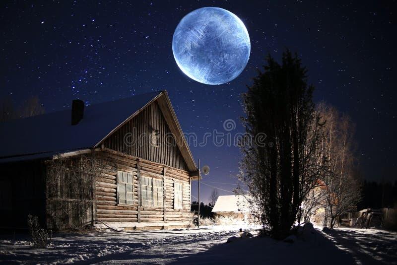 Lunes peu communes au-dessus de village d'hiver image stock