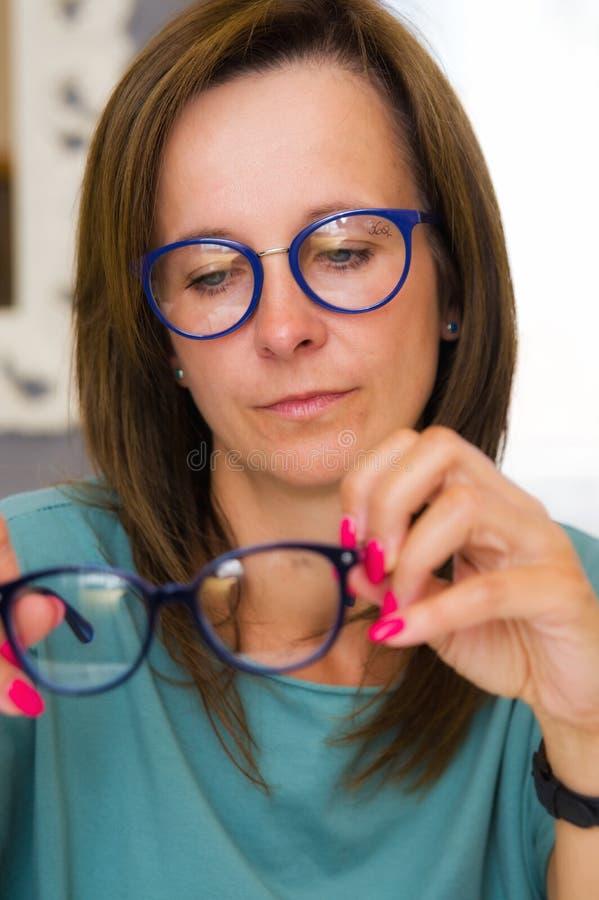 Lunettes de choix et de achat de femme de brune dans le salon ou le magasin d'opticien photos libres de droits