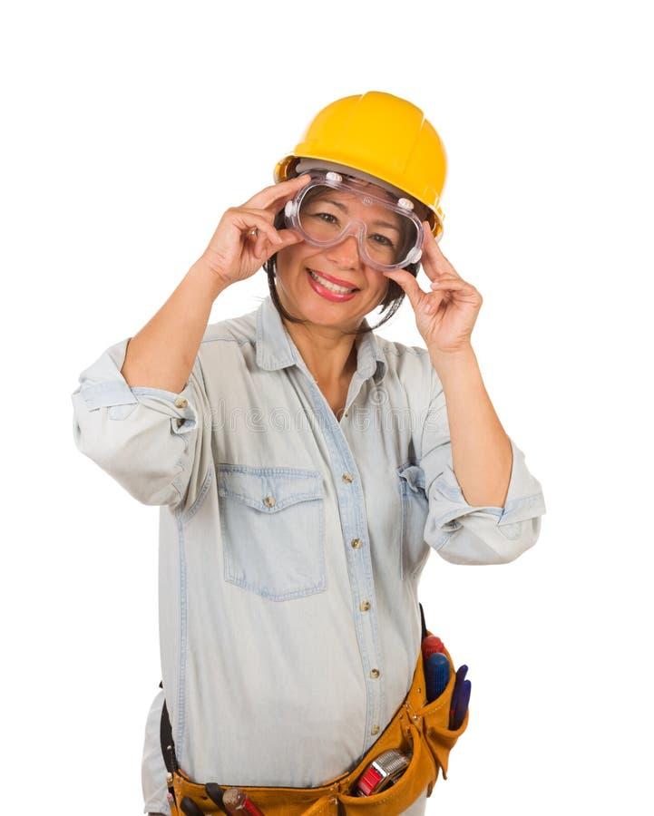 Lunettes de port d'entrepreneur femelle hispanique, casque antichoc et lunettes d'isolement sur le fond blanc photos libres de droits