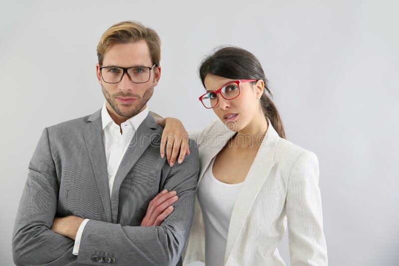 Lunettes de port de couples élégants d'affaires photographie stock