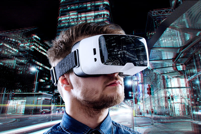 Lunettes de port de réalité virtuelle d'homme contre la ville de nuit photos stock