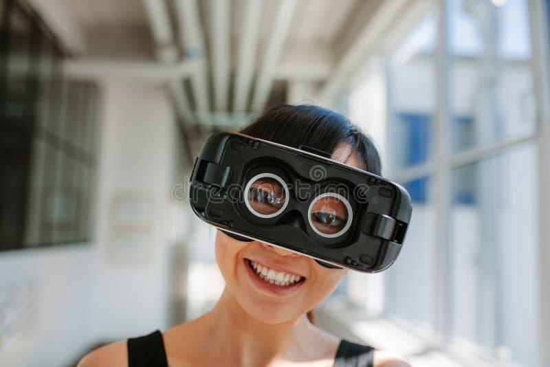 Lunettes de port de réalité virtuelle de jeune femme gaie images stock