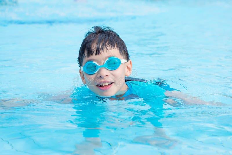 Lunettes de port de jeune garçon nageant dans la piscine photos stock