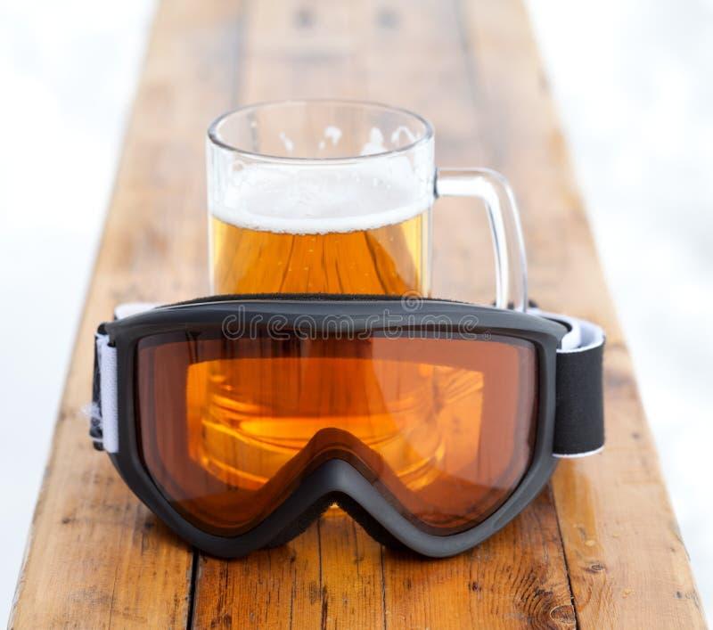 Lunettes de ski et tasse en verre avec de la bière froide fraîche photo stock