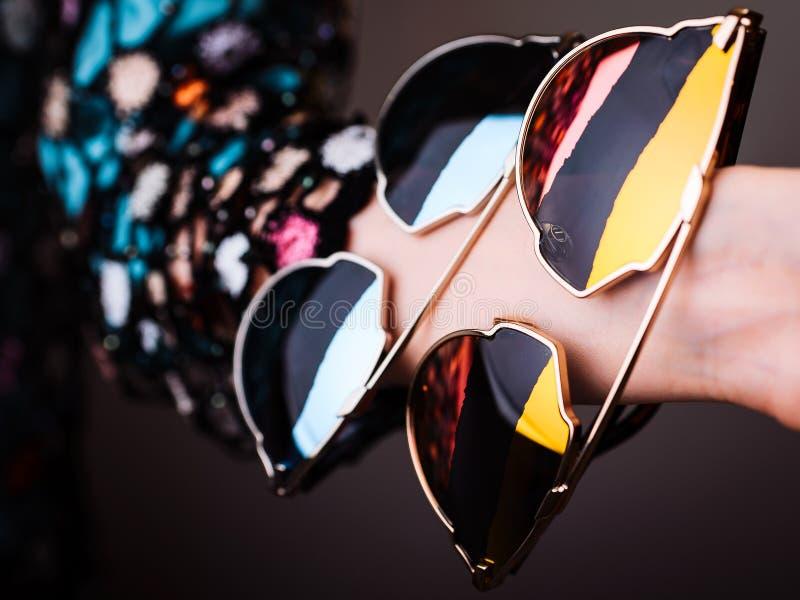 Lunettes de soleil à la mode avec les lentilles multicolores en main photographie stock libre de droits