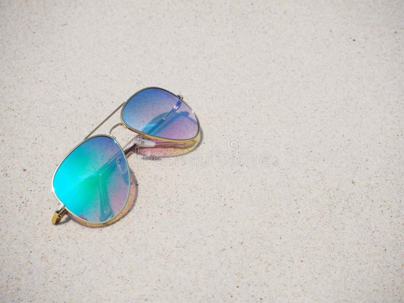 Lunettes de soleil à la mode de miroir sur le sable photos stock