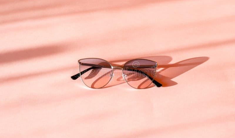 Lunettes de soleil élégantes modernes de cadre en métal sur le fond de papier rose à la mode au soleil Configuration plate ?t? de photos stock