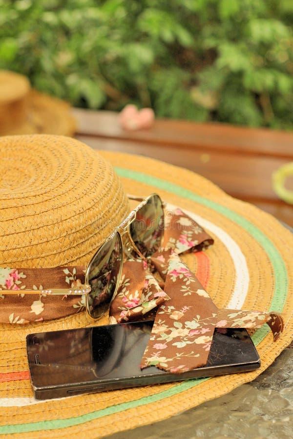 Lunettes de soleil avec des chapeaux de paille, smartphone photo libre de droits