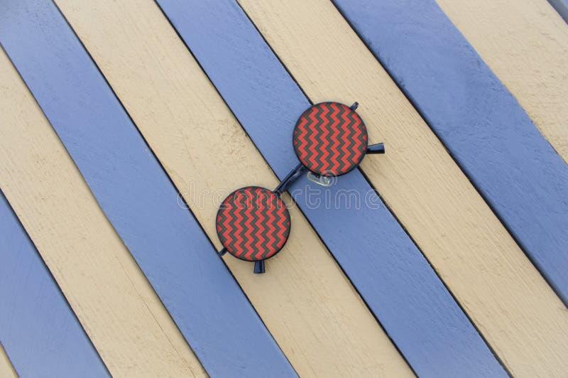 Lunettes de soleil créatives sur une surface rayée photos stock