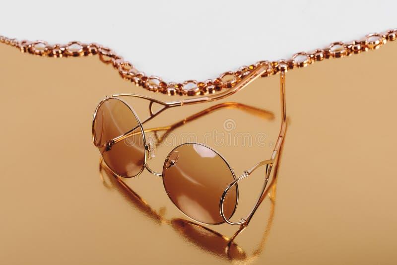 Lunettes de soleil d'élite dans un cadre à la mode moderne en métal sur un fond d'or image libre de droits
