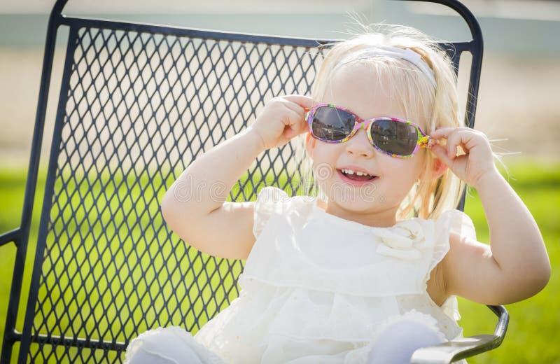 Lunettes de soleil de port de bébé espiègle mignon dehors au parc photographie stock libre de droits
