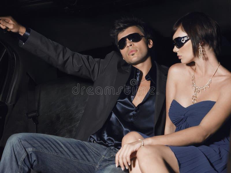 Lunettes de soleil de port de couples de célébrité dans la limousine photographie stock