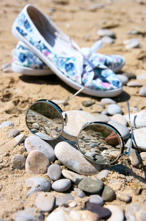 Lunettes de soleil et chaussures des femmes sur la plage photo libre de droits