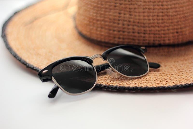 Lunettes de soleil et un chapeau de paille photographie stock libre de droits
