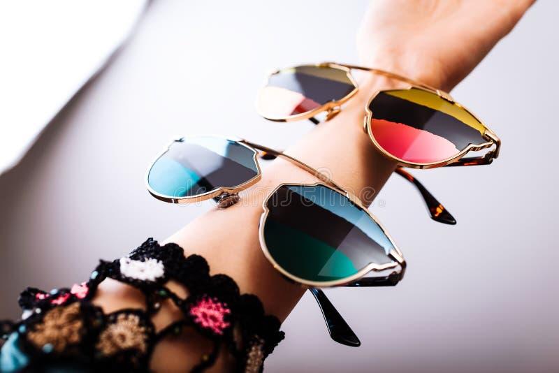 Lunettes de soleil ? la mode avec les lentilles multicolores en main photos stock