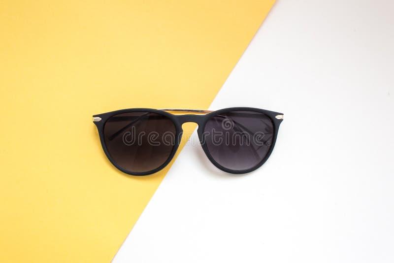 lunettes de soleil noires sur le fond blanc et jaune mode de minimalisme et d'été pour la plage images libres de droits