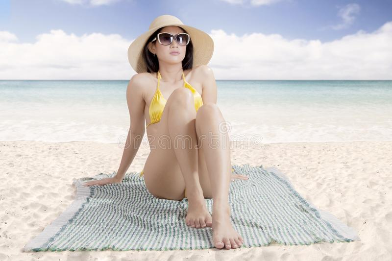 Lunettes de soleil de port de belle femme seul prenant un bain de soleil photographie stock