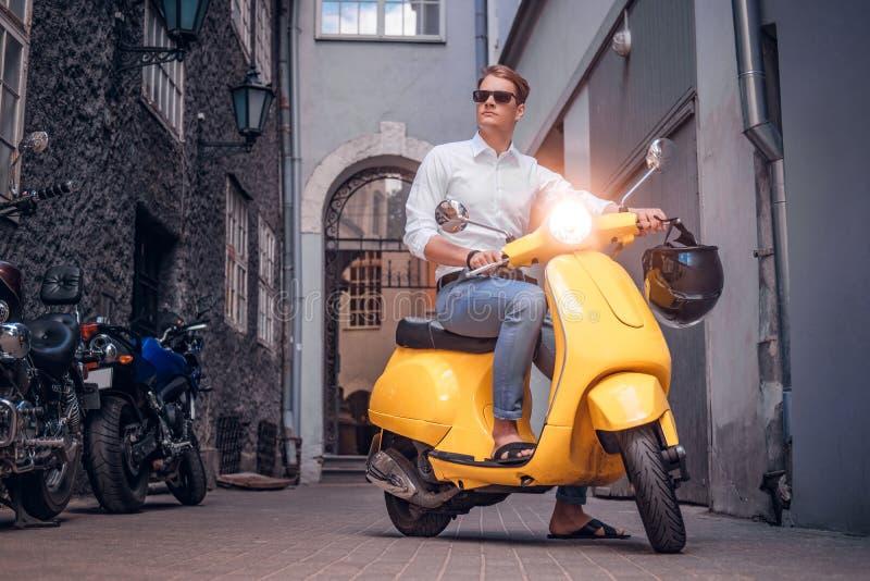 Lunettes de soleil de port d'homme bel montant sur le scooter italien de cru dans la vieille rue étroite de l'Europe photos libres de droits