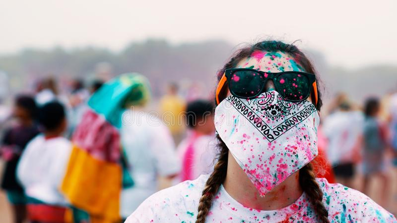 Lunettes de soleil de port de femme et couvert de son visage de bandana pendant une fiesta de peinture photographie stock