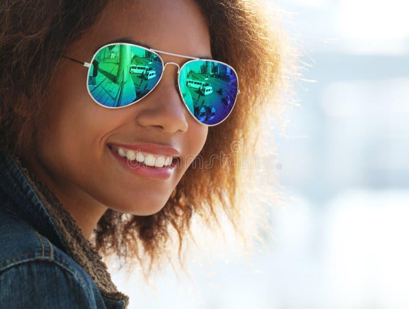 Lunettes de soleil de port de jolie femme avec les dents parfaites et la peau propre fonc?e ayant le repos dehors images stock