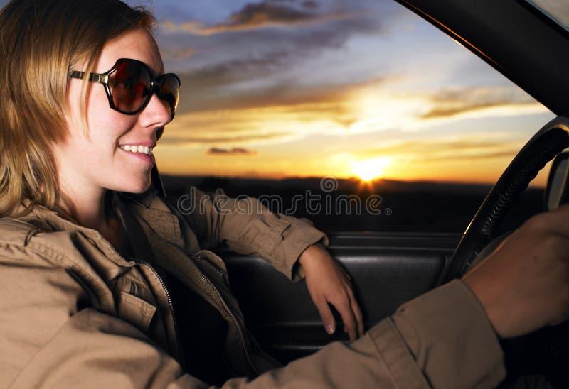 Lunettes de soleil s'usantes de jeune femme souriant et pilotant photo libre de droits