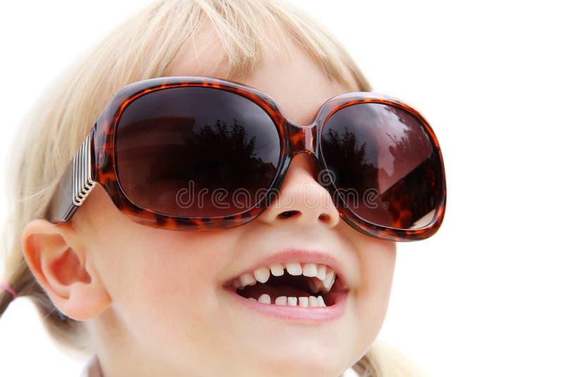 Lunettes de soleil s'usantes mignonnes de petite fille image stock