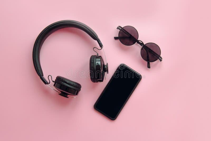 Lunettes de soleil, smartphone et écouteurs noirs élégants sur le backg rose photos libres de droits