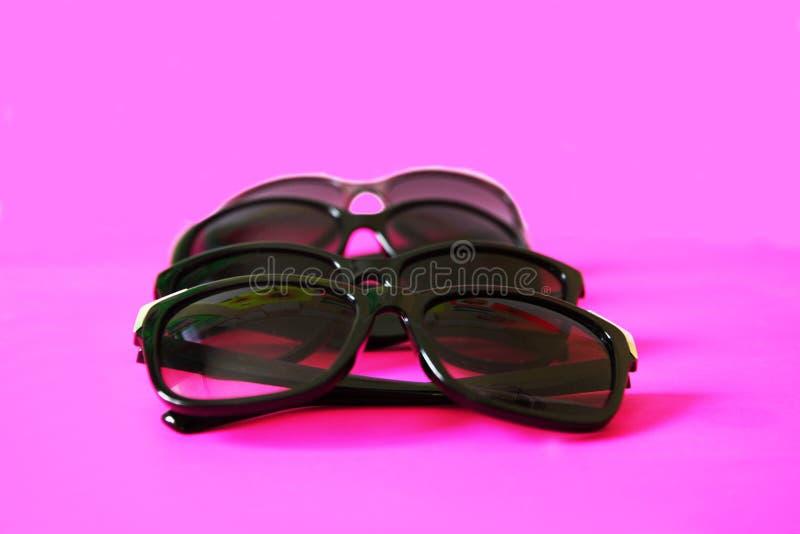 Lunettes de soleil sur le fond en pastel Verres avec les cadres noirs Accessoires de mode UV de protection d'oeil image stock