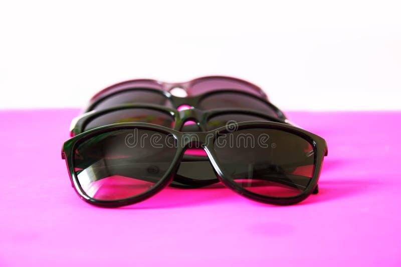Lunettes de soleil sur le fond en pastel Verres avec les cadres noirs Accessoires de mode UV de protection d'oeil photographie stock