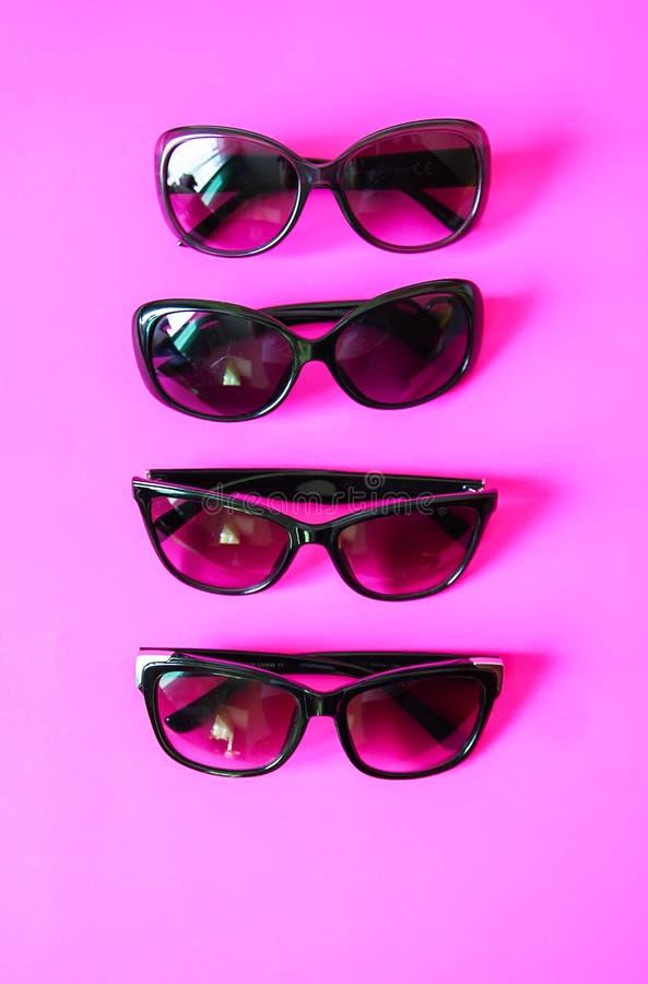 Lunettes de soleil sur le fond en pastel Verres avec les cadres noirs Accessoires de mode UV de protection d'oeil photo libre de droits