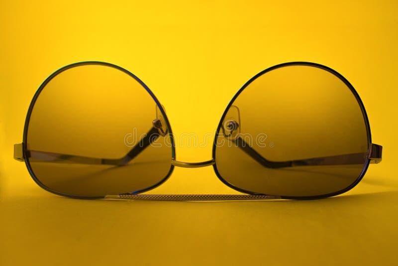 Lunettes de soleil sur le fond jaune images stock