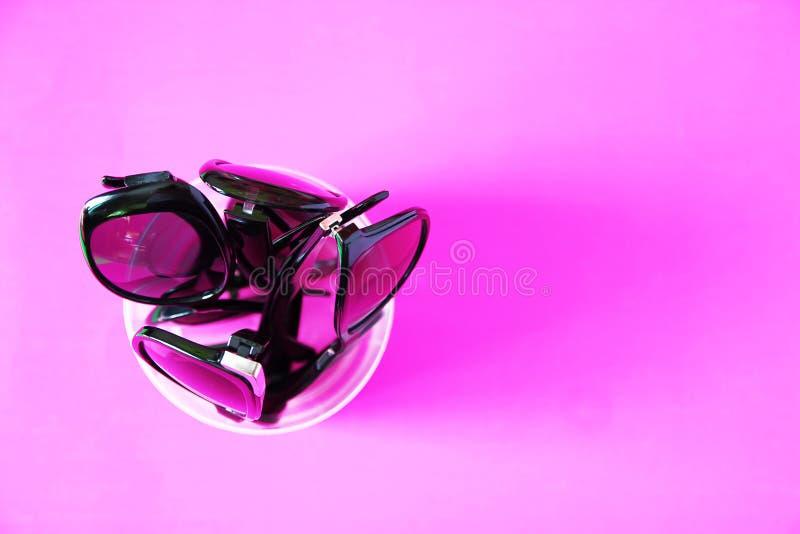 lunettes de soleil sur le fond rose Verres avec les cadres noirs Accessoires de mode UV de protection d'oeil photographie stock libre de droits