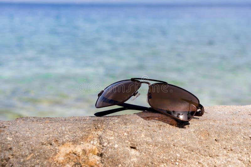 Lunettes de soleil sur une pierre avec le fond bleu de mer photos libres de droits
