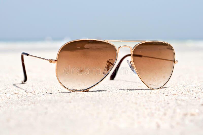 Lunettes de soleil sur une plage de sable image stock