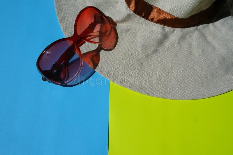 Lunettes de Sun, chapeau sur le fond bleu et jaune photos libres de droits
