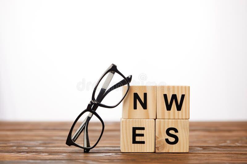 lunettes et cubes en alphabet faisant des actualités de mot sur la surface en bois, sur le fond blanc photographie stock libre de droits