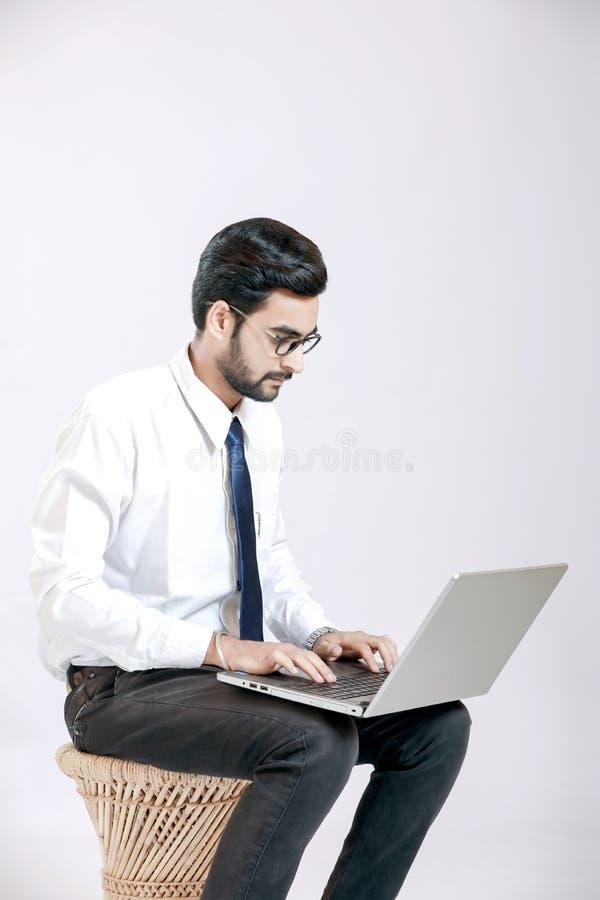 Lunettes indiens d'usage de jeune homme et travailler sur l'ordinateur portable photos stock