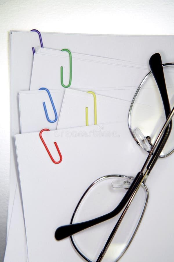Lunettes sur des papiers image stock