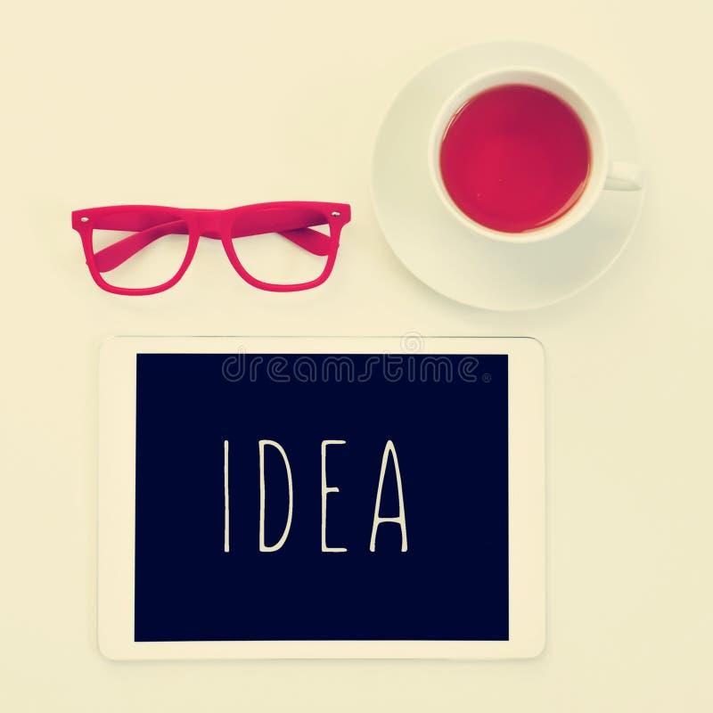 Lunettes, tasse de thé et idée de mot dans une tablette photographie stock libre de droits