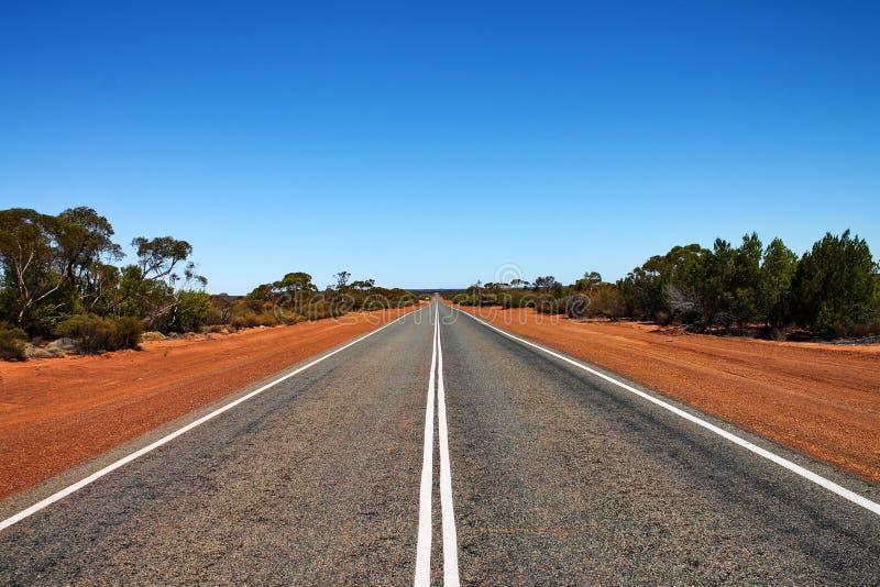 Lungamente, strada vuota con l'entroterra australiana fotografia stock