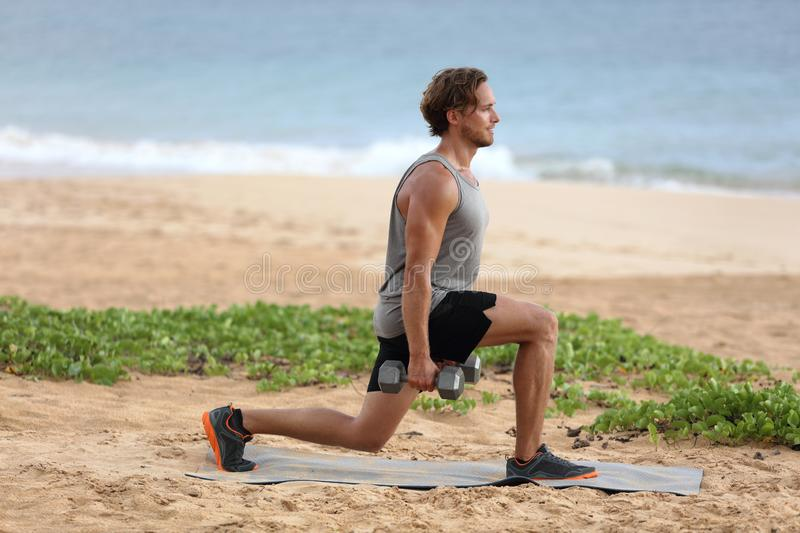 Lunge exercise fitness man training lunges exercising legs muscles with dumbbell weights. Male fitness model doing alternating stock photo